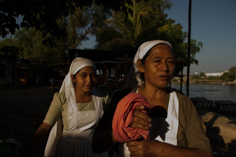 Two evangelical women from Guatemala serve free coffee and atole to people crossing the Suchiate River. Photo by Gabriela Bortolamedi.