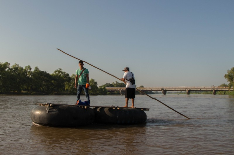 Two men cross the Suchiate River, which borders Guatemala and Mexico. In the background, we can see a bridge that houses a migratory checkpoint. Photo by Gabriela Bortolamedi.
