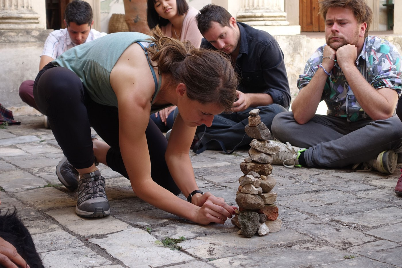 Lacie places her stone while others observe (nervously). Photo by Diana Taylor.